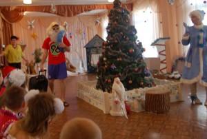 Входит Дед Мороз в шортах, футболке, солнцезащитных очках, в белом парике, бороде. Несет надувной круг, чемодан, ест банан?!!!!!
