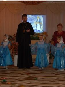 Дети внимательно слушают поздравления духовного наставника