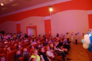 Дети с шарами проходят в зрительский зал