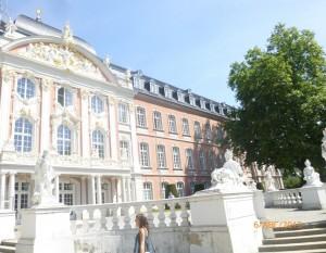 С южной стороны базилики в середине 18 века пристроили нарядный дворец, Дворец Курфюрстов — один из наиболее значительных памятников барокко Трира. Строительство дворца закончено 1761 году.