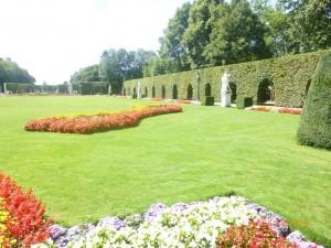 Перед дворцом вереница статуй, резные изгороди дугообразной формы и большой водоем украшают великолепные сады