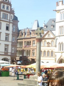 Рыночный крест, воздвигнутый в 958 году, как символ торгового мира и церковной власти над городом. За ним -красно-бежевый дом со звездочкой на фасаде (на нем есть надпись, утверждающая, что Трир старше Рима на 1,300 лет???)