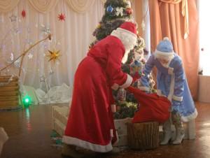 Дед Мороз – (хитро)  Волшебство я начинаю. (из колодца достает подарки)